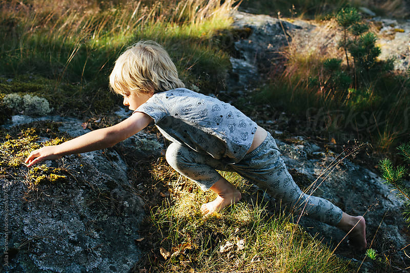 Boy stretches while climbing barefoot on rocks. by Julia Forsman for Stocksy United