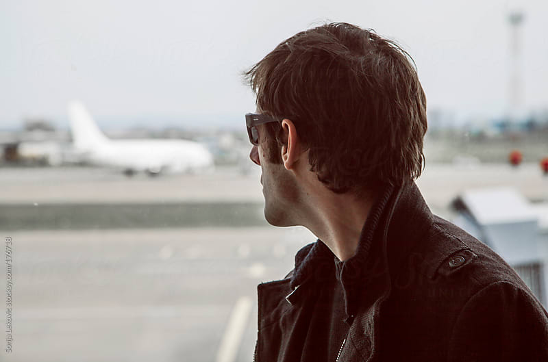 man from behind looking at an airplane by Sonja Lekovic for Stocksy United