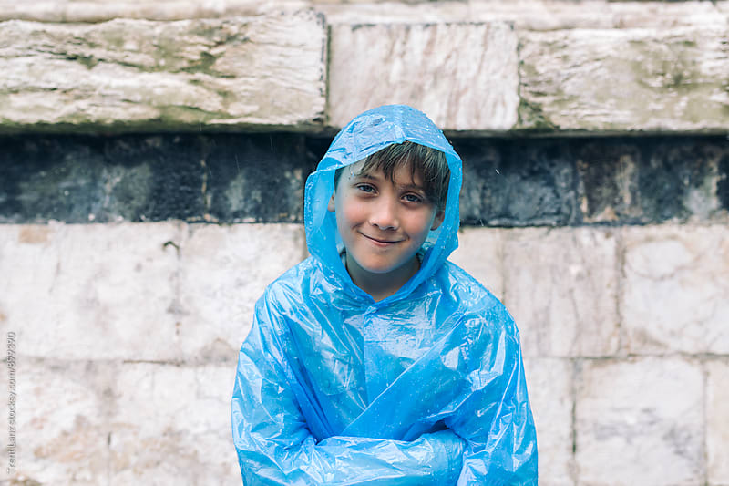 Cheerful boy wearing wet raincoat smiling in the rain by Trent Lanz for Stocksy United