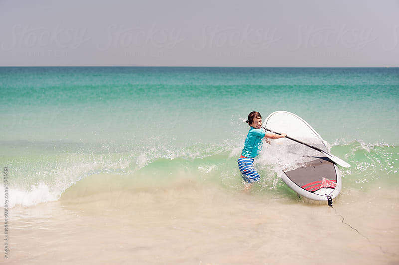 Boy with a stand up paddle board at the beach by Angela Lumsden for Stocksy United