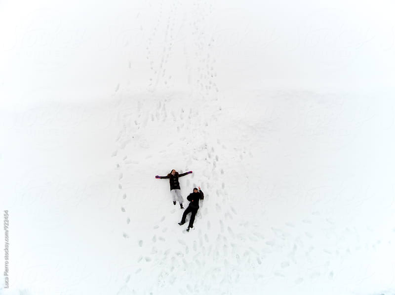 Aerial view of two friends having fun on the snow by Luca Pierro for Stocksy United