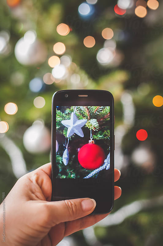 Woman taking a photo of christmas tree ornaments with an Android mobile phone by Lea Csontos for Stocksy United