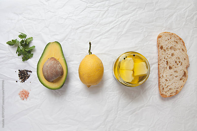 Ingredients for making smashed avocado on toast with feta for breakfast by Natalie JEFFCOTT for Stocksy United