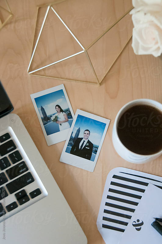 Polaroid pictures of bride and groom on a busy desk by Jovo Jovanovic for Stocksy United