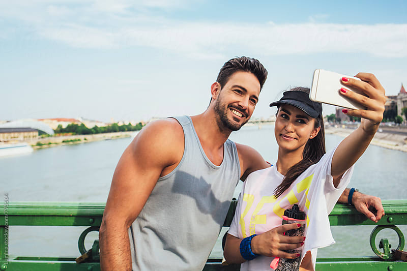 Couple in Fitness Clothes Taking a Selfie by Lumina for Stocksy United