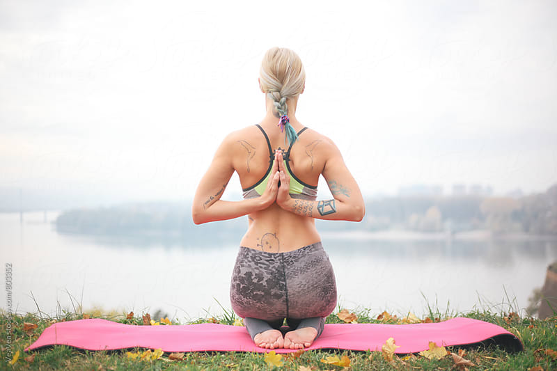 Woman practicing yoga outdoors by VeaVea for Stocksy United