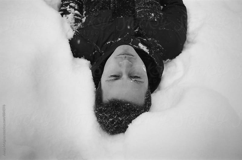 A black and white film portrait of young men lying on the snow by Anna Malgina for Stocksy United