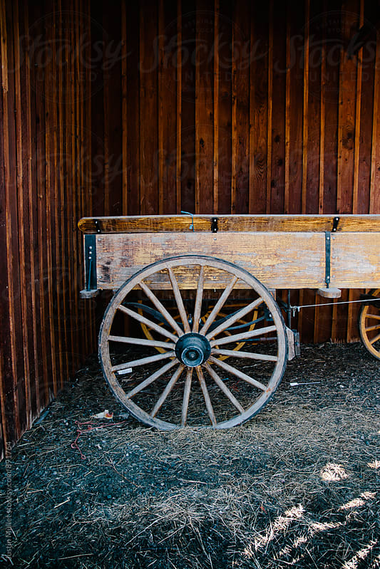 A old carriage against a stained wood wall by Justin Mullet for Stocksy United