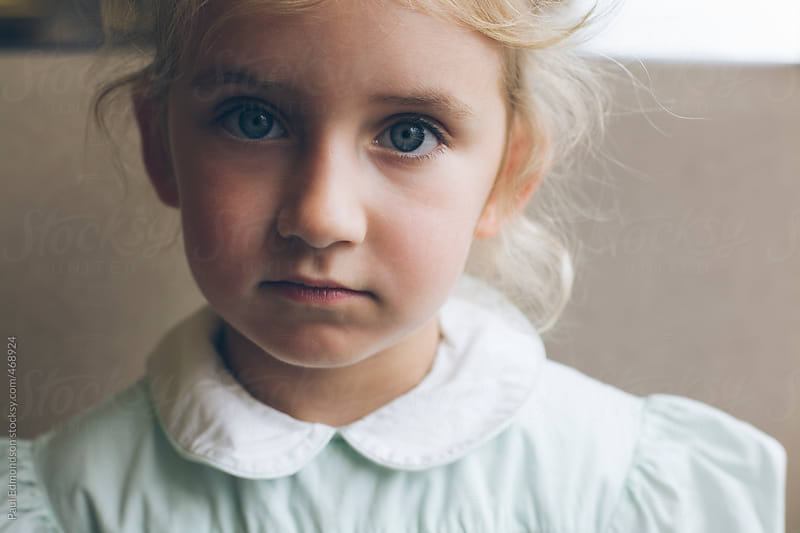 Portrait of serious four year old girl by Paul Edmondson for Stocksy United