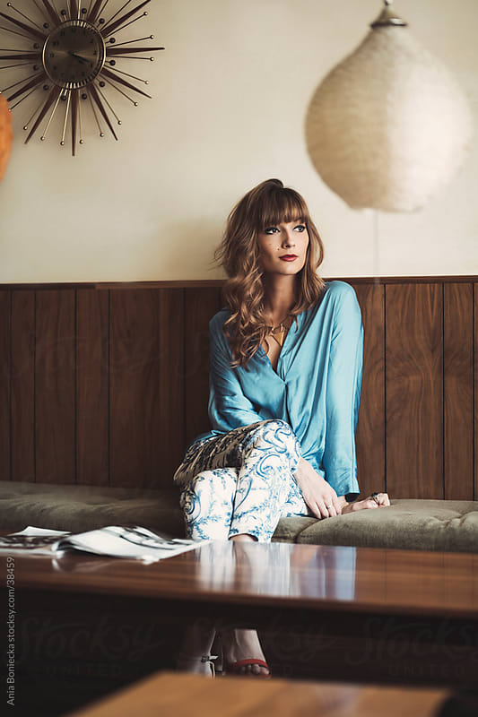 A beautiful woman in a retro interior relaxing on a bench with a magazine on the table by Ania Boniecka for Stocksy United