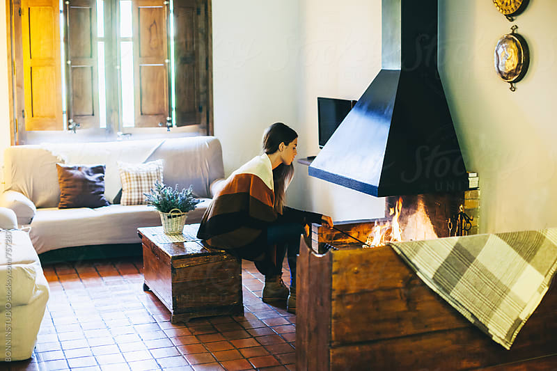 Woman warming up by the fireplace at home. by BONNINSTUDIO for Stocksy United