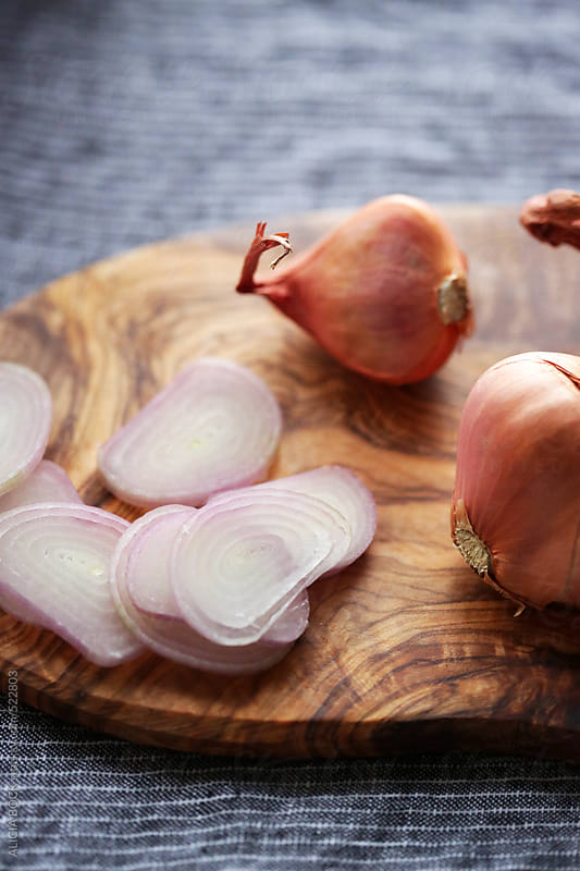 Fresh Cut Shallots On A Wood Cutting Board by ALICIA BOCK for Stocksy United