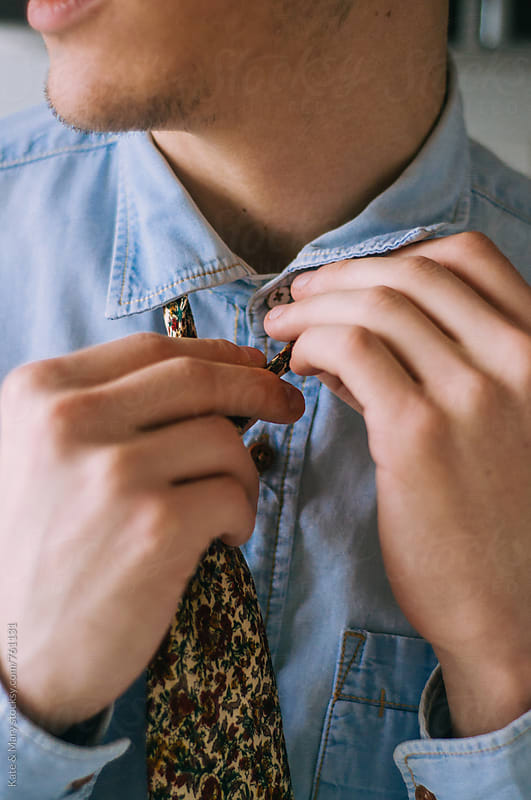 Young man setting up a tie by Kate & Mary for Stocksy United