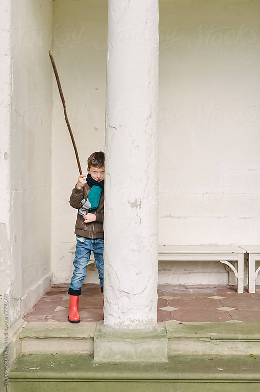 Child hiding behind doric column by Rebecca Spencer for Stocksy United