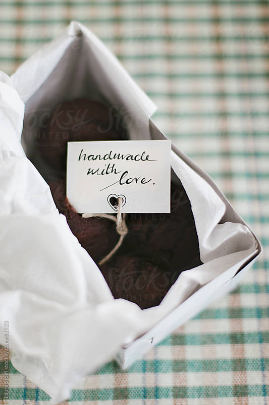 Overhead shot of chocolate muffin in box with loving tag by Laura Stolfi for Stocksy United