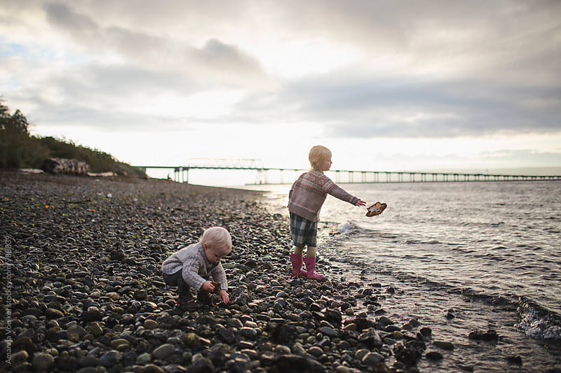 A Little Girl Throws a Crab Shell into the water while Her brother plays by Amanda Voelker for Stocksy United
