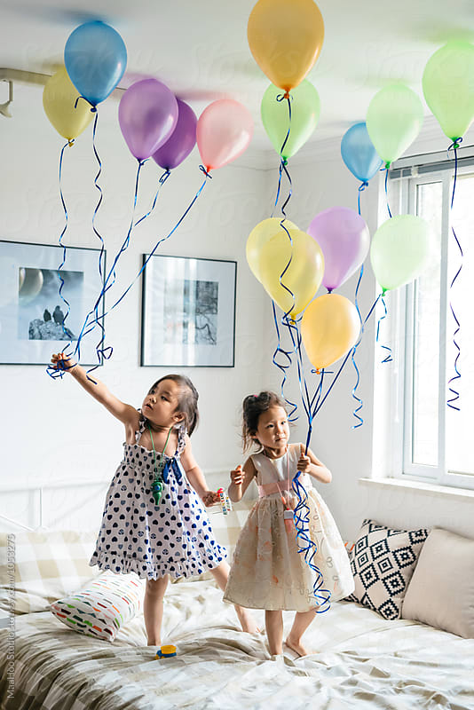 Kids playing with balloons by Maa Hoo for Stocksy United