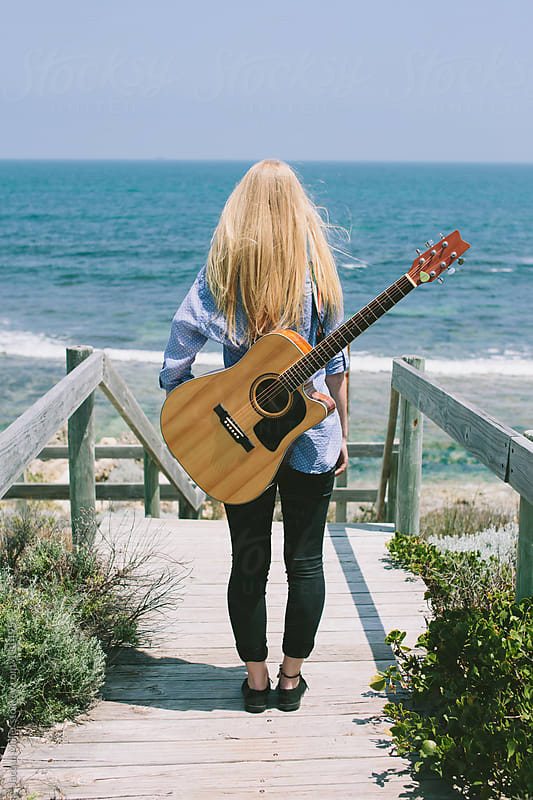 Girl, with a guitar on her back, stands and looks at the ocean.  by Jacqui Miller for Stocksy United