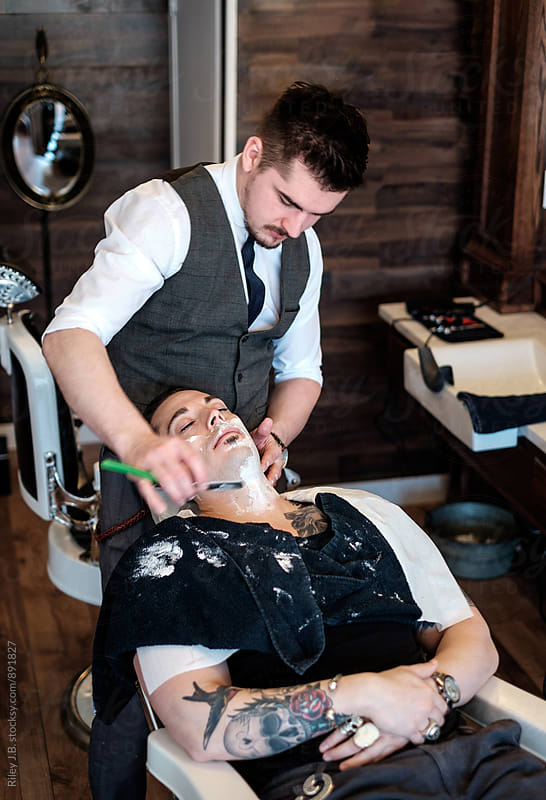 A gentleman barber shaves a client's neck with a classic straight razor. by Riley Joseph for Stocksy United