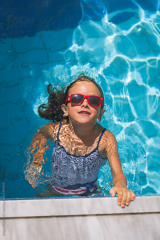 Little girl swimming in the pool by Dejan Ristovski for Stocksy United