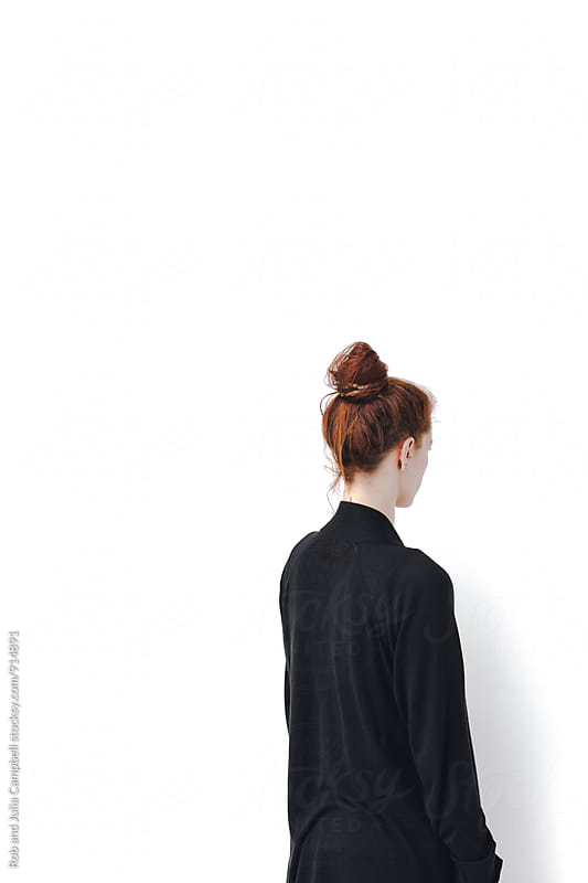 Stark anonymous image of the back of a red headed woman and white wall by Rob and Julia Campbell for Stocksy United