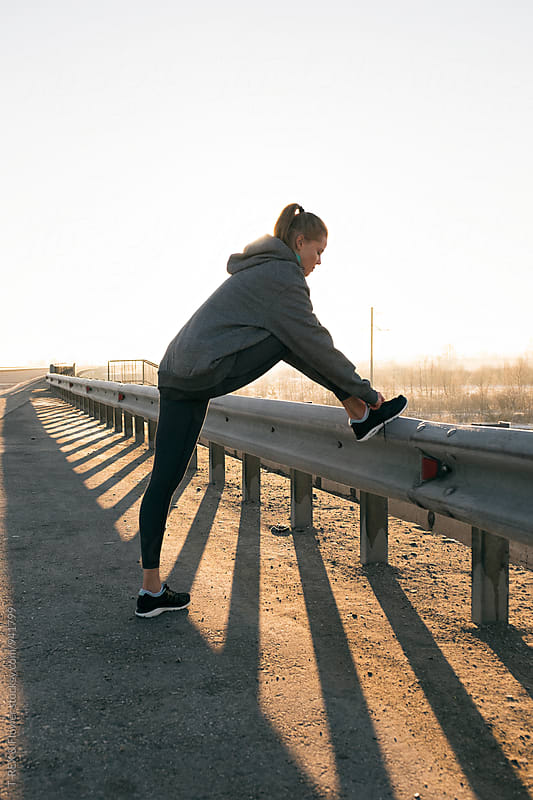 Sportswoman tying laces on roadside  by Danil Nevsky for Stocksy United