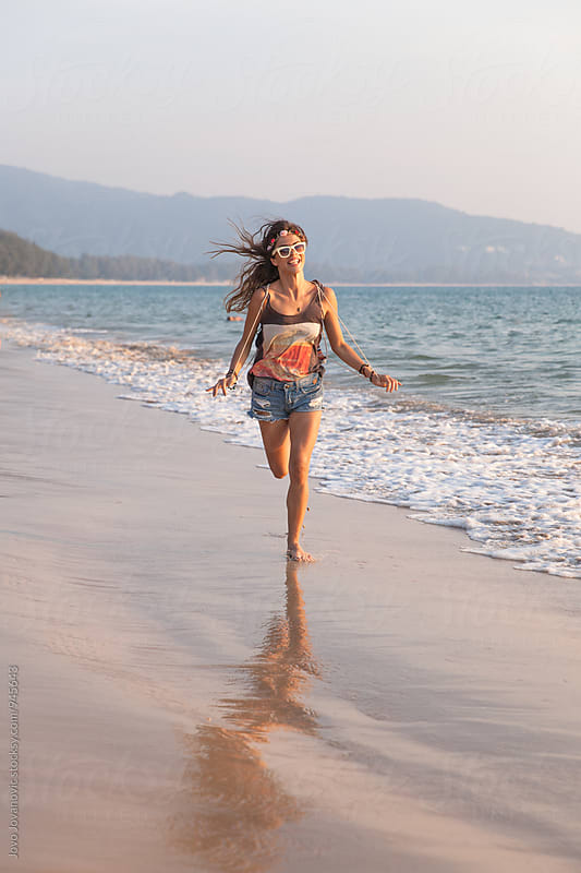 Young and wild - woman running at the sea shore by Jovo Jovanovic for Stocksy United