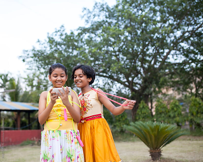 Two girls previewing the photograph taken by selfie by PARTHA PAL for Stocksy United