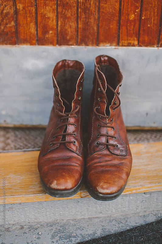 Vinage brown laced  up boots in front of old doors by Sanja (Lydia) Kulušić for Stocksy United