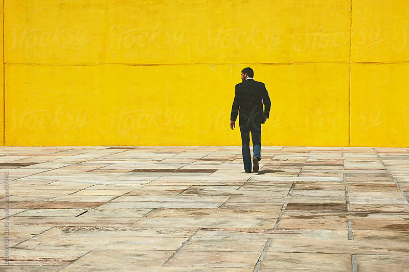 Businessman walking on the street in front a yellow big wall. by BONNINSTUDIO for Stocksy United
