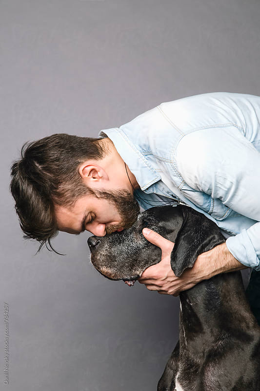 Bearded man kissing his dog by Danil Nevsky for Stocksy United