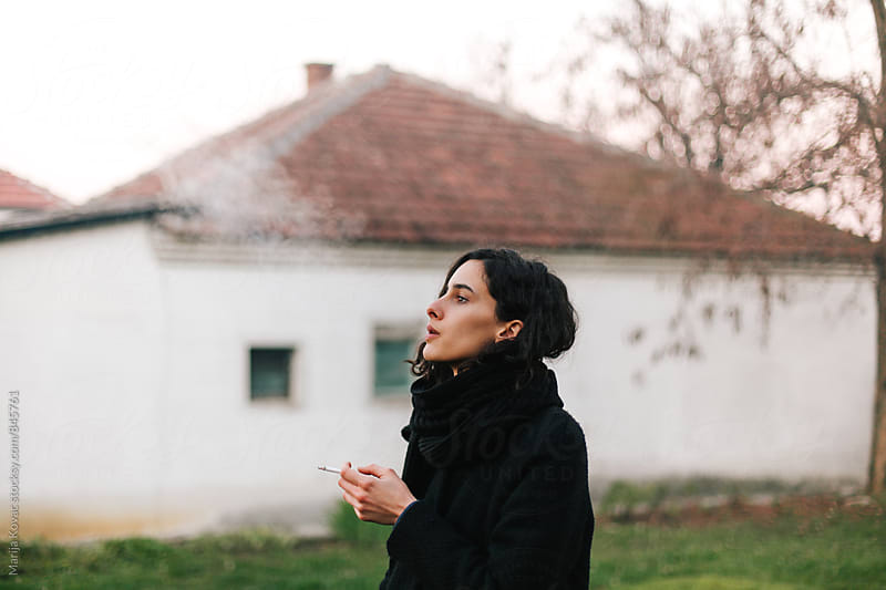 Beautiful young woman smoking cigarette in front of a house  by Marija Kovac for Stocksy United