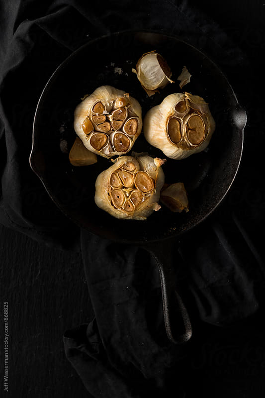 Roast Garlic in Cast Iron Pan by Jeff Wasserman for Stocksy United