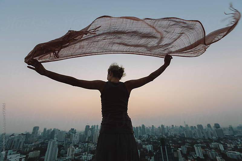 Woman looking the cityscape from the roof by michela ravasio for Stocksy United