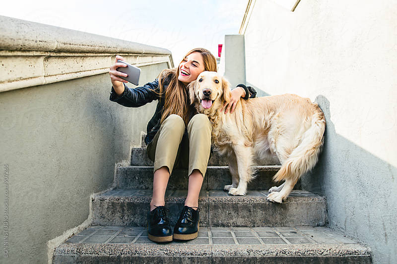 Woman sitting on stairs taking a selfie with her dog. by BONNINSTUDIO for Stocksy United