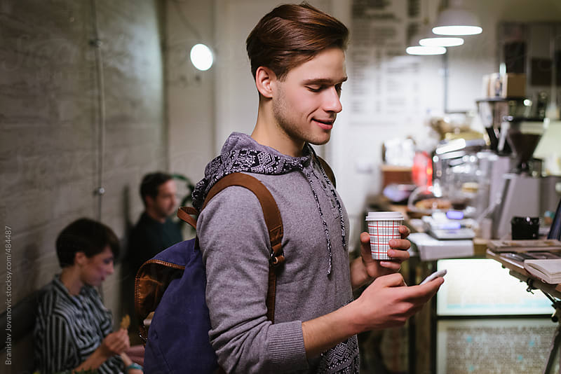 Young man texting on his phone in a coffee shop by Brkati Krokodil for Stocksy United