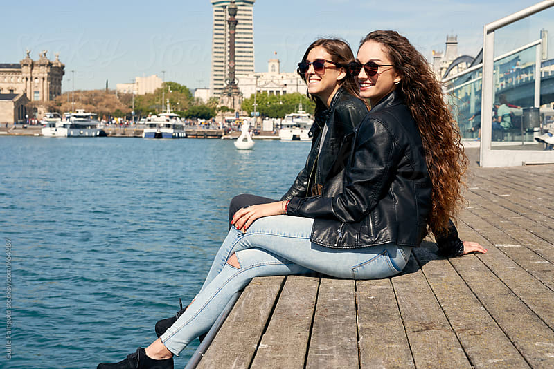 Two young girlfriends sitting on wooden pier by Guille Faingold for Stocksy United