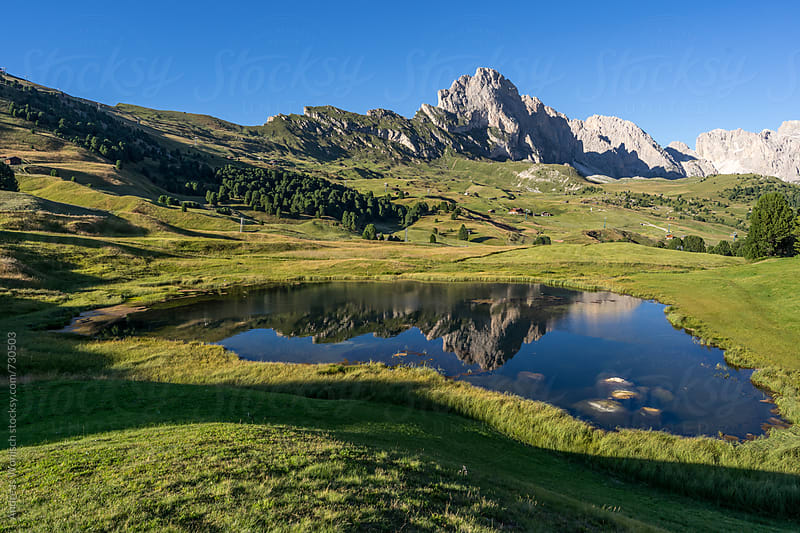View over a lake and mountains in the Dolomites by Andreas Wonisch for Stocksy United