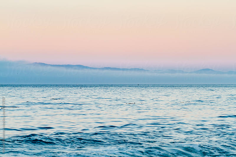 Purple sunset over ocean with mountains and fog on the horizon by Mihael Blikshteyn for Stocksy United