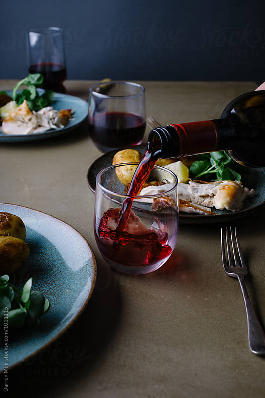 Roast chicken: With rosemary and lemon. Pouring red wine. by Darren Muir for Stocksy United