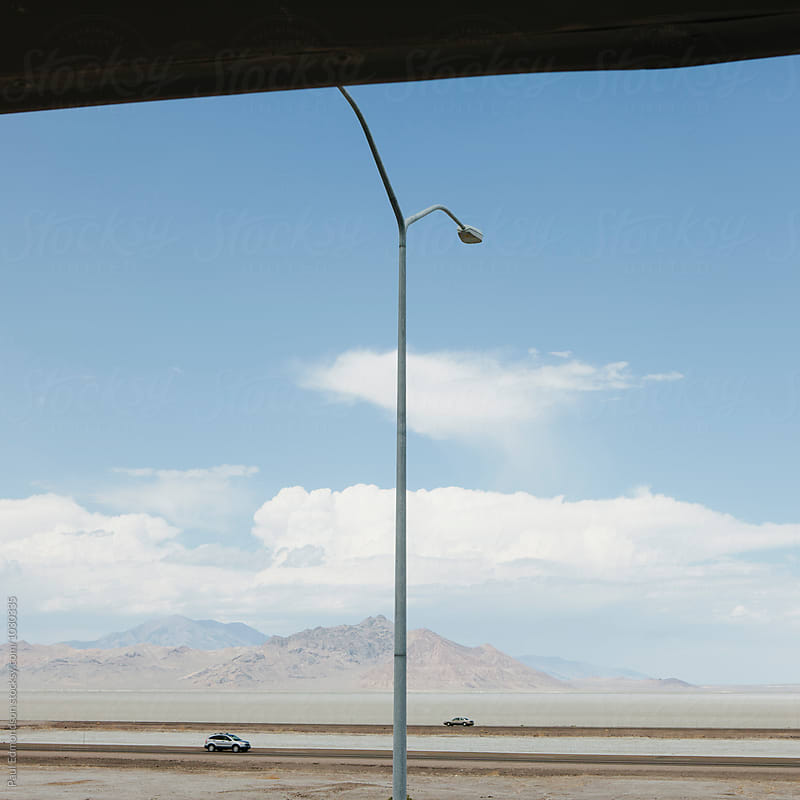 Cars driving on desolate desert highway, overpass in foregound by Paul Edmondson for Stocksy United
