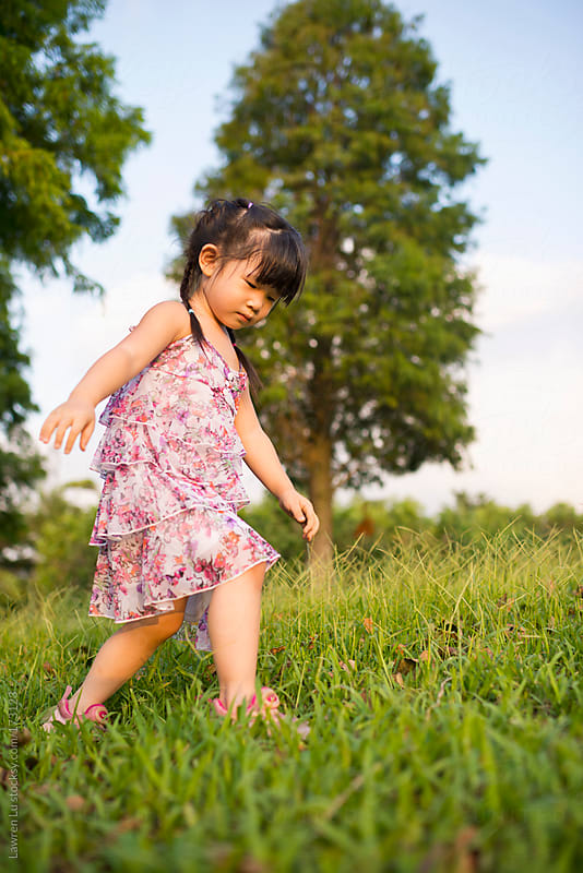Little girl walking on the grassland by Lawren Lu for Stocksy United