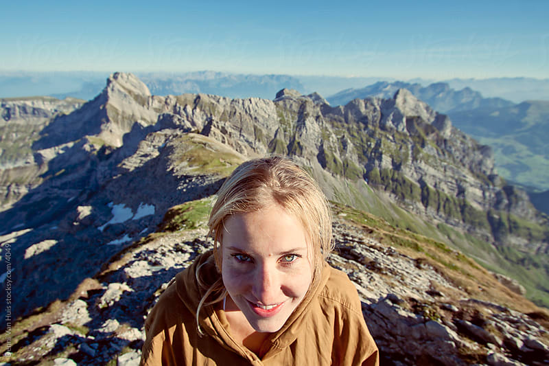 Young woman playing up on the mountain tops. by Denni Van Huis for Stocksy United