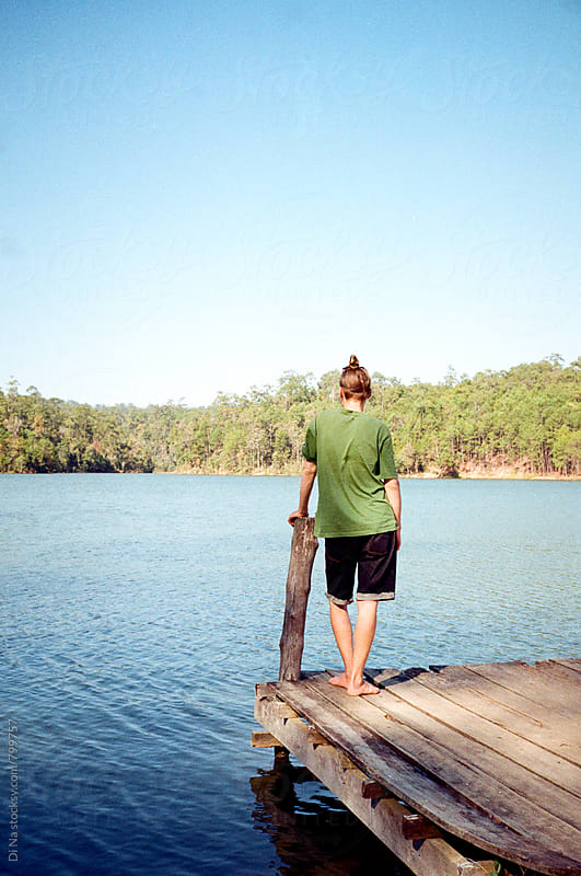 Young man standing on the shore of the lake by Dina Lun for Stocksy United