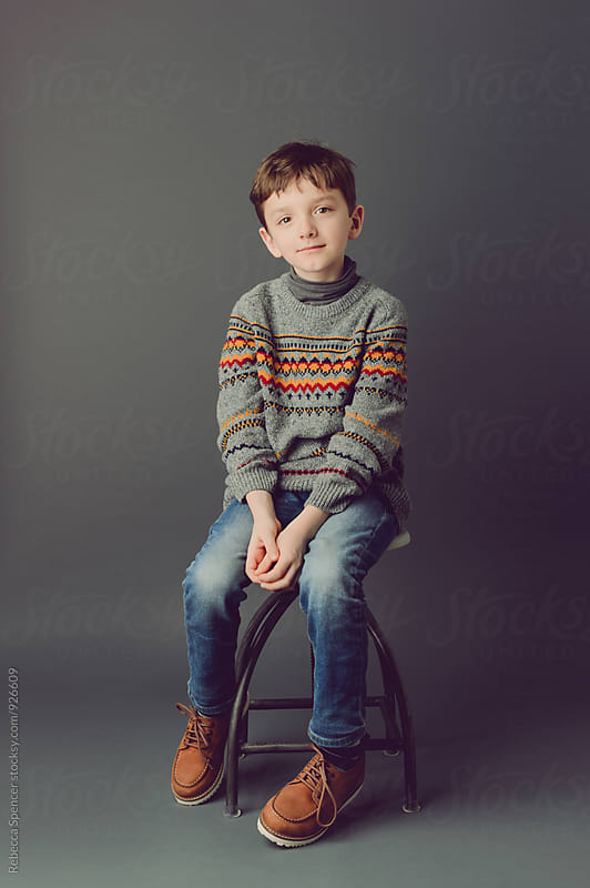 Portrait of a young boy sitting on a stool by Rebecca Spencer for Stocksy United
