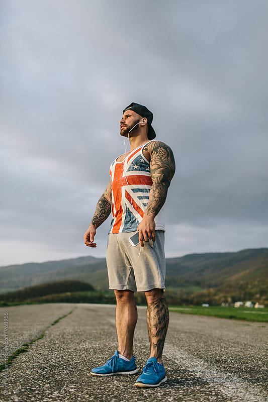Sporty Tattooed Man  by Peter Meciar for Stocksy United