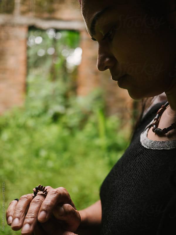 Dark girl looking at her clay ring by Martin Matej for Stocksy United