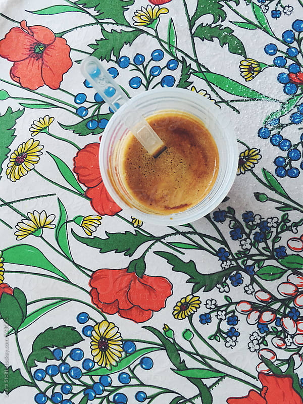 Coffee break at office: overhead shot of disposable coffee cup and sugar on flowered background by Laura Stolfi for Stocksy United