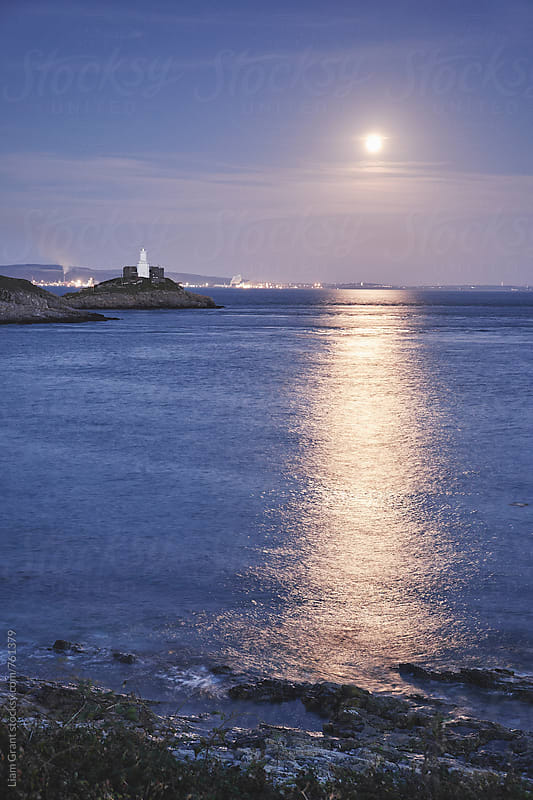 Full moon and lighthouse at Mumbles Head. Wales, UK. by Liam Grant for Stocksy United