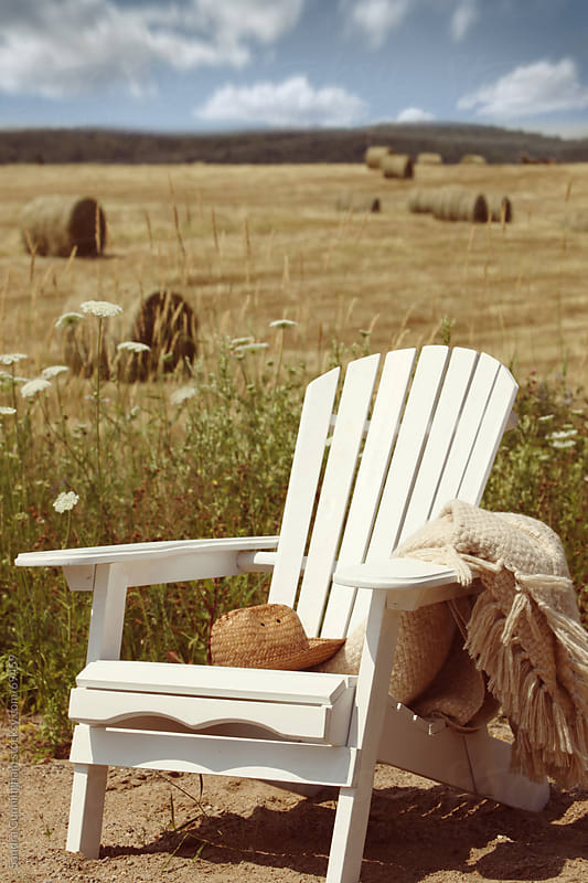 Adirondack chair overlooking bales of hay in field  by Sandra Cunningham for Stocksy United
